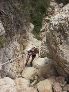 Climbing down a rope to reach the beach