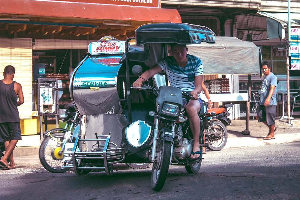 guy on a motorized tricycle in the Philippines