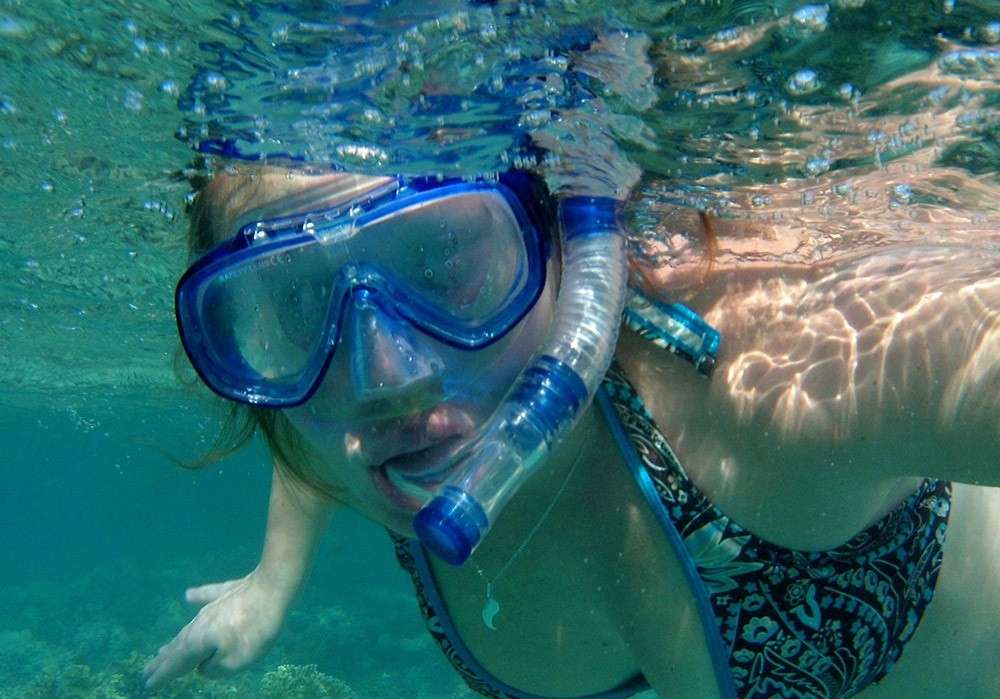 woman snorkeling with a fogged up mask