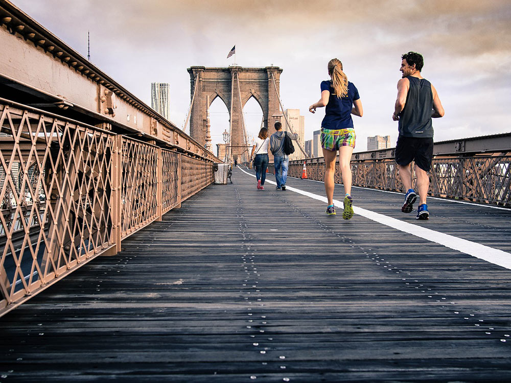 a couple going for a run across the Brooklyn Bridge