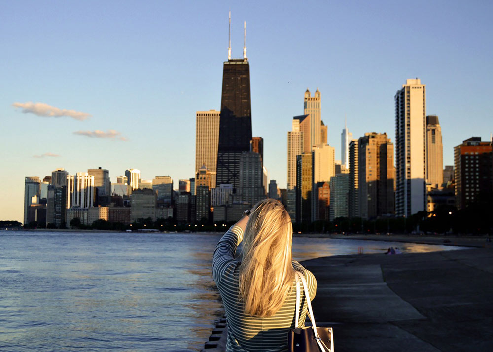 woman taking a picture of Chicago's skyline